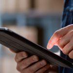 primer plano de unas manos con una tablet haciendo control de inventario en un almacén