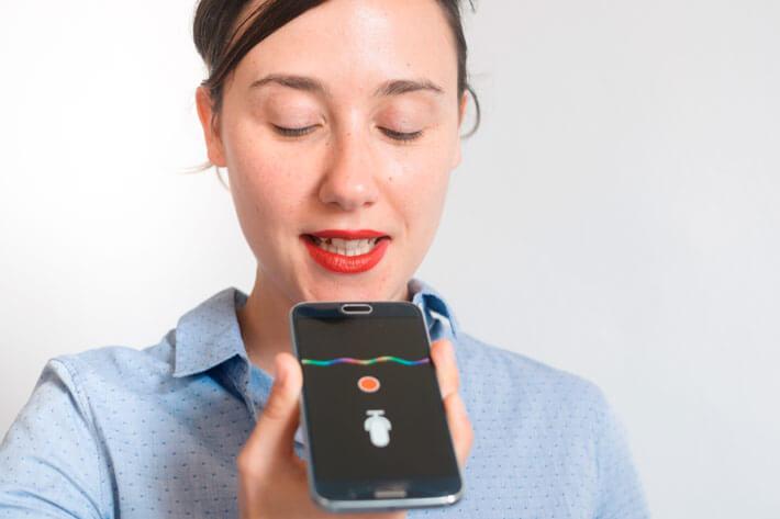 Mujer hablándole a su asistente virtual con su móvil